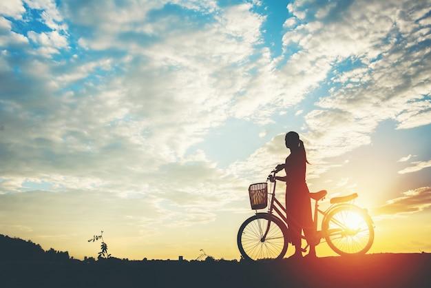 Sylwetka kobiety z rowerowym i pięknym niebem