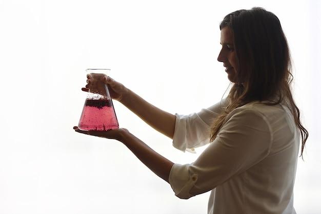 Sylwetka kobiety z różową butelką eliksiru, koncepcja fitoterapii, białe tło