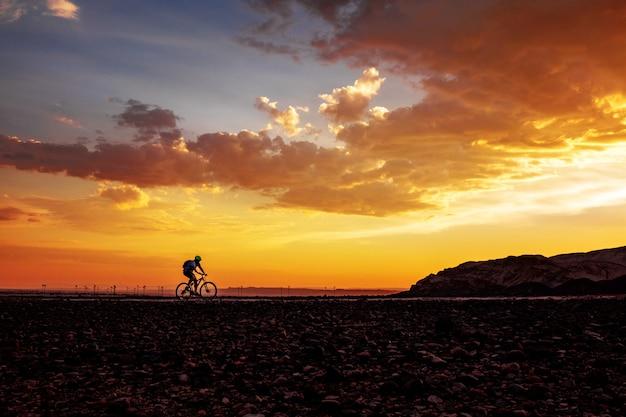 Sylwetka kolarstwo mężczyzna na rowerze na pięknym zmierzchu tle