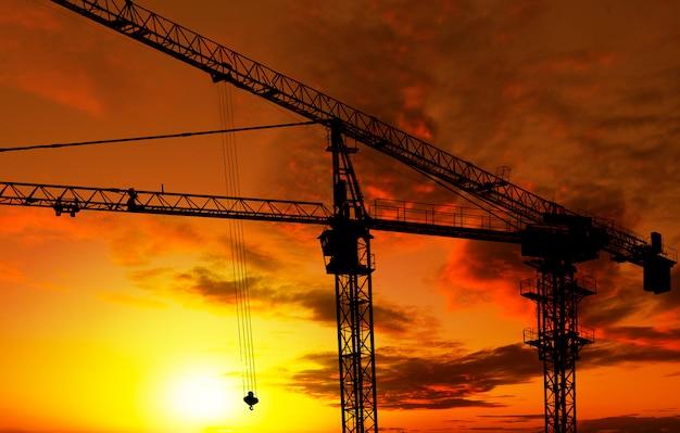 Sylwetka konstrukcji budynku dźwig wieże o zachodzie słońca.