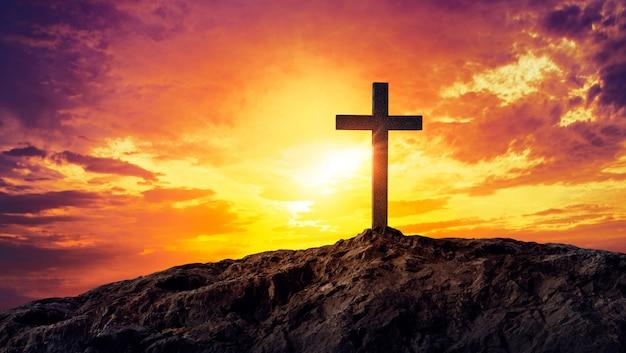 Sylwetka krzyża chrześcijanina na górze o zachodzie słońca