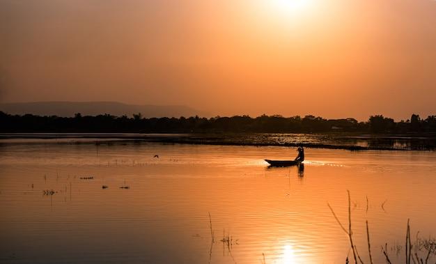 Sylwetka łódź rybacka z zachodem słońca