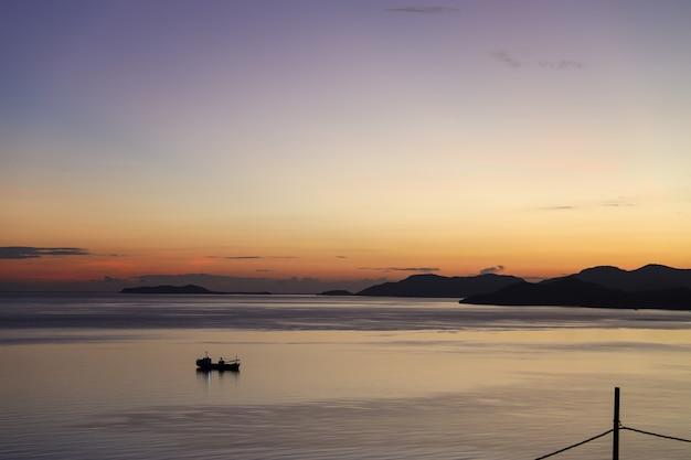 Sylwetka łodzi rybackiej płynącej po morzu podczas wschodu słońca z fioletowym i pomarańczowym niebem