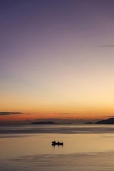 Sylwetka łodzi rybackiej płynącej po morzu podczas zachodu słońca z pięknym niebem