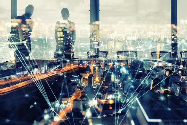 Sylwetka ludzi biznesu nad oświetlonym nowoczesnym miastem z efektami sieci