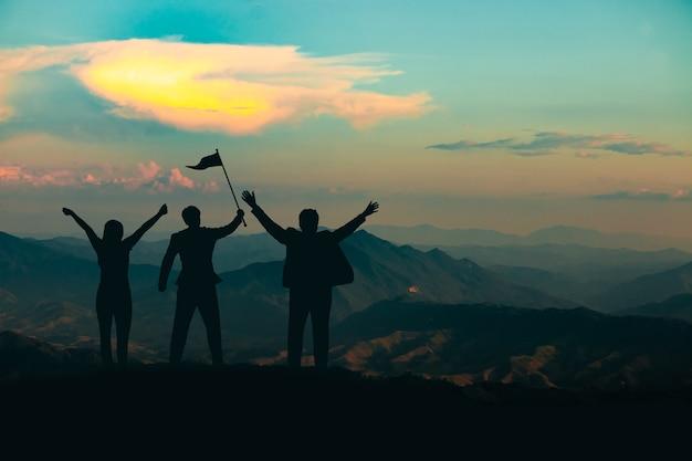 Sylwetka ludzi na szczycie góry na tle nieba i światła słonecznego, biznes, sukces, przywództwo, osiągnięcia i koncepcja ludzi