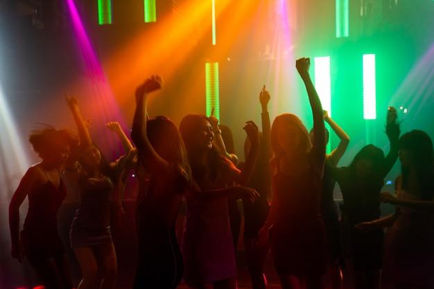 Sylwetka ludzi tańczy w dyskotece przy muzyce z dj na scenie