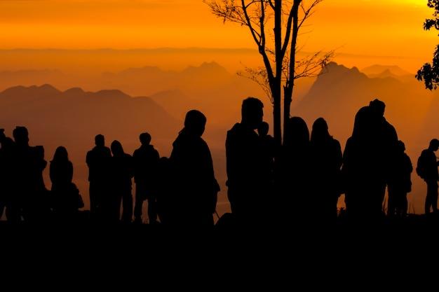 Sylwetka ludzi zrelaksować się na klifie i górach z zachodem słońca w godzinach wieczornych
