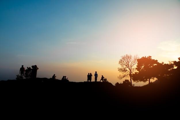 Sylwetka ludzi zrelaksować się w górach o zachodzie słońca wieczorem.