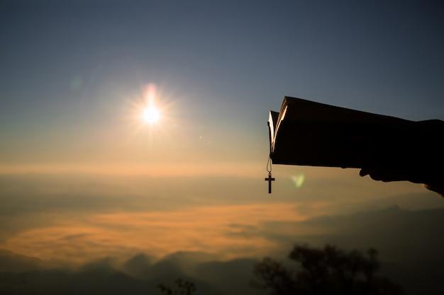 Sylwetka ludzka ręka trzyma biblię i krzyż, tło jest wschodem słońca