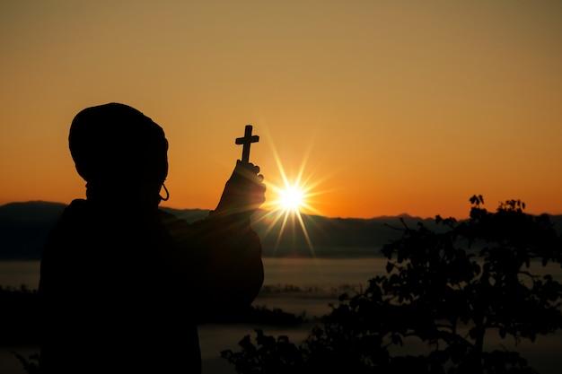 Sylwetka ludzka ręka trzyma krzyż tło jest wschodem słońca