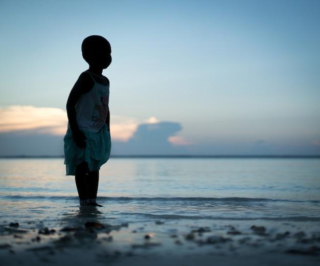 Sylwetka mała dziewczynka na plaży