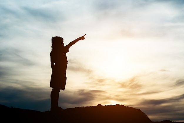 Sylwetka małej dziewczynki dźwigania ręka wolności szczęśliwy czas