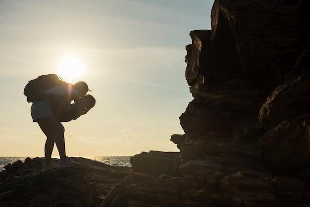 Sylwetka mama pocałować i przytulić swojego chłopca dziecko na łuku brzegu plaży z morzem zachód słońca, park narodowy khao laem ya, rayong, tajlandia. letnie rodzinne wakacje w siam, tropikalny kraj.