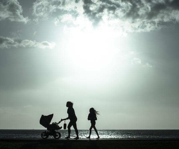 Sylwetka matki pchania wózka dziecięcego z dziewczyna spacer