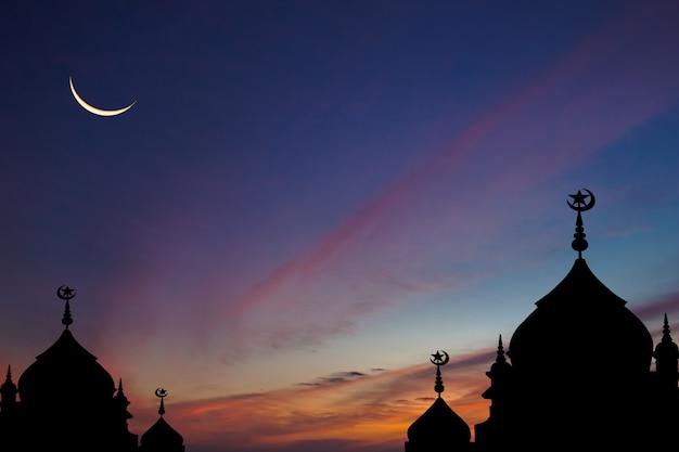 Sylwetka meczety na ciemnoniebieskim niebie i półksiężyc na tle zmierzchu