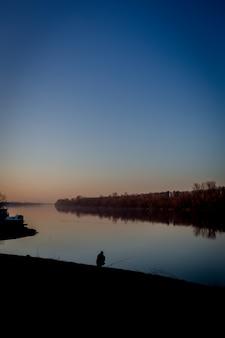 Sylwetka męski obsiadanie blisko wody pod jasnym niebieskim niebem w vertical strzale