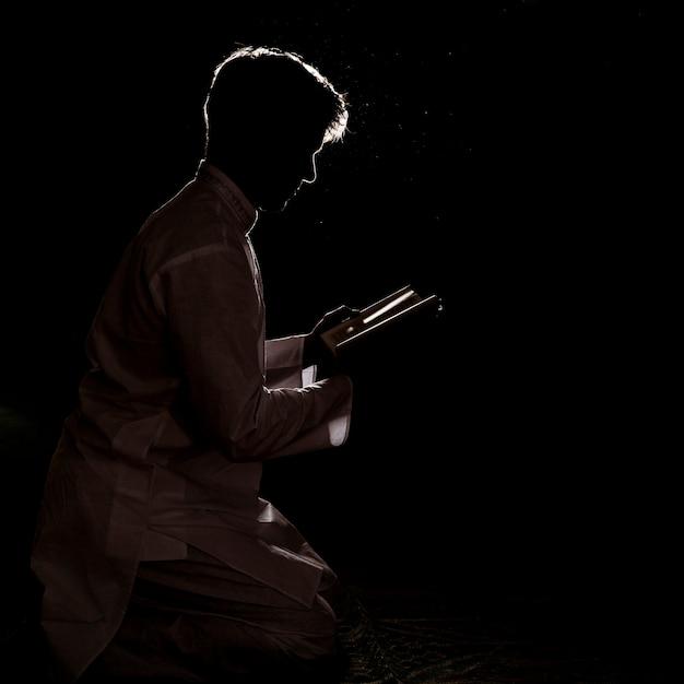 Sylwetka mężczyzna czytanie w koranie