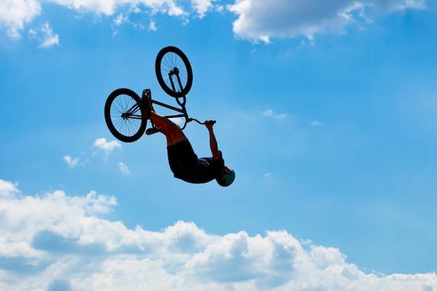 Sylwetka mężczyzna doskakiwanie na bicyklu przeciw niebieskiemu niebu z białymi chmurami. facet wykonuje sztuczki na rowerze