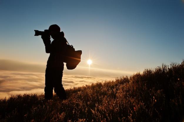 Sylwetka mężczyzna fotograf z kamerą na ręki tła górach na zmierzchu z mgłą