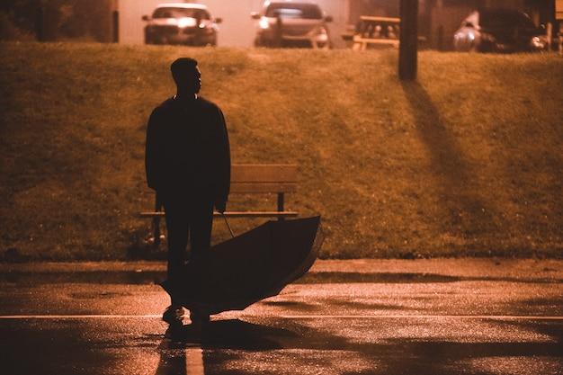 Sylwetka mężczyzna mienia parasol podczas nocy