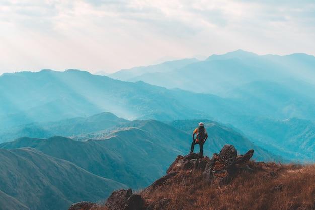Sylwetka mężczyzna podtrzymywał ręki na szczycie góra, sukcesu pojęcie