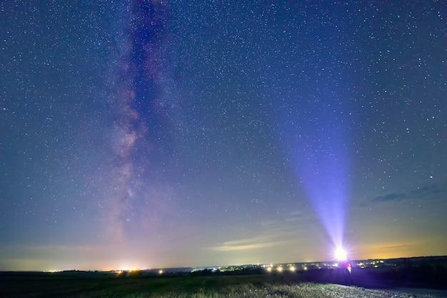 Sylwetka mężczyzny i ślad latarki na tle gwiaździstego nieba z częścią h galaktyki drogi mlecznej.