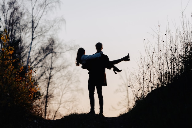Sylwetka mężczyzny, który trzyma dziewczynę w ramiona. widok z tyłu.