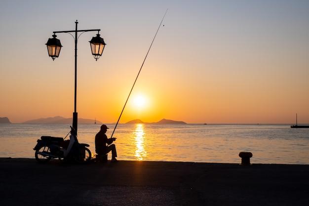 Sylwetka mężczyzny łowiącego ryby na molo o zachodzie słońca
