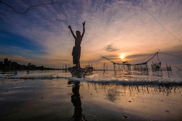 Sylwetka mężczyzny na łodzi łowi małe ryby w jeziorze jako atrakcja turystyczna w prowincji phatthalung w południowej tajlandii 8.08.2018