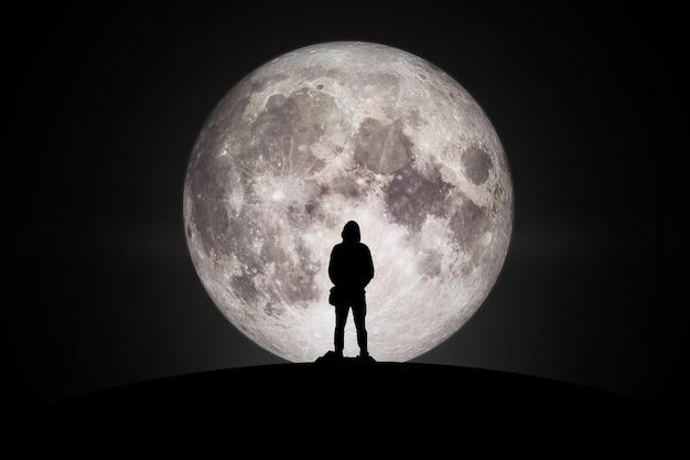 Sylwetka mężczyzny patrząc na księżyc w miłości elementy tego obrazu dostarczone przez nasa