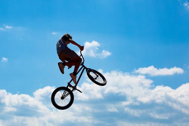 Sylwetka mężczyzny skaczącego na rowerze na tle błękitnego nieba z białymi chmurami. facet wykonuje sztuczki na rowerze