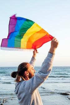 Sylwetka mężczyzny trzymającego tęczową flagę dumy gejowskiej wiejącej na wietrze na tropikalnej plaży ze złotym słońcem