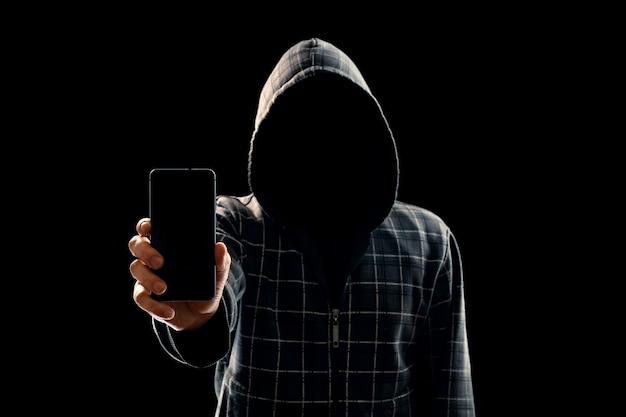 Sylwetka mężczyzny w kapturze na czarnym tle, jego twarz nie jest widoczna, haker trzyma telefon w dłoniach