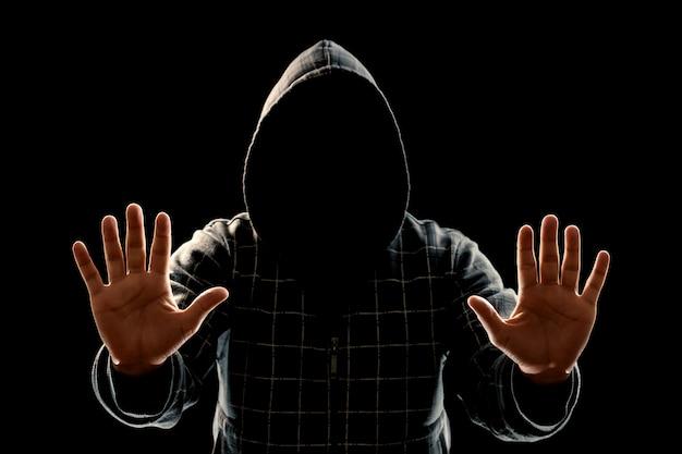 Sylwetka mężczyzny w kapturze na czarnym tle, twarz nie jest widoczna, pokazuje dłonie w aparacie.
