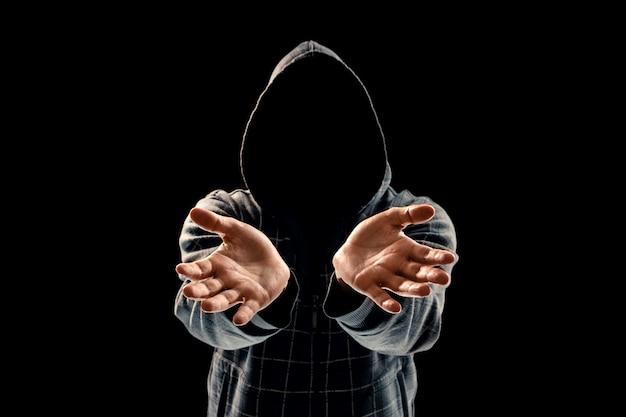 Sylwetka mężczyzny w kapturze na czarnym tle, twarz nie jest widoczna, pokazuje dłonie