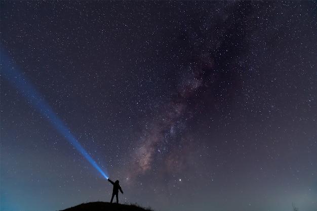 Sylwetka mężczyzny z latarką, obserwująca piękne, szerokie błękitne niebo nocne z gwiazdami i galaktyką drogi mlecznej. astronomia, orientacja, czyste niebo