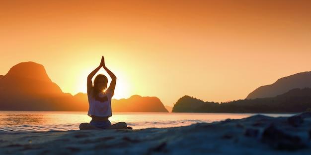 Sylwetka młoda kobieta praktykuje jogę na plaży o zachodzie słońca