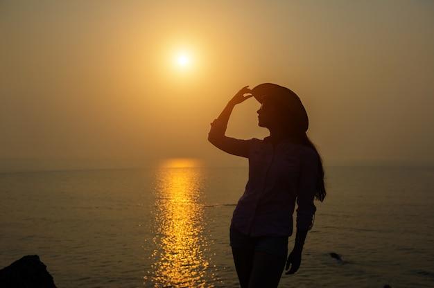 Sylwetka młoda kobieta w kapeluszu przeciw zmierzchowi nad morzem