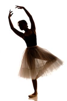 Sylwetka młoda piękna balerina w białej spódniczce baletnicy i pointe butach robi taniec pozie