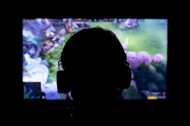 Sylwetka młodego człowieka, grając w gry wideo za pomocą słuchawek i konsoli