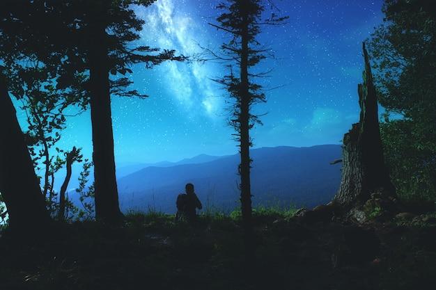 Sylwetka młodego człowieka siedzącego na skraju tarasu widokowego i cieszącego się nocnym krajobrazem z gwiaździstym niebem i pełnią księżyca