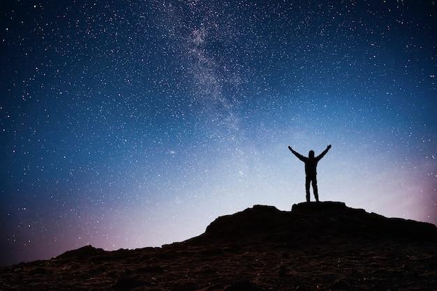 Sylwetka młodego człowieka tło galaktyki drogi mlecznej na jasnym, ciemnym niebie ciemnego nieba