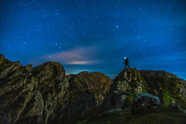 Sylwetka młodego człowieka w nocy na górze aiako harria w oiartzun. kraj basków