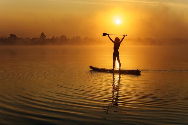 Sylwetka młodego człowieka z atletyczna budowa ciała, stojąc na pokładzie sup i trzymając wiosło nad głową.