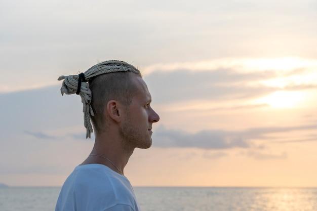 Sylwetka młodego faceta z dredami na głowie w pobliżu morza podczas zachodu słońca. zamknij się portret. szczęśliwy przystojny mężczyzna z dredami na tropikalnej plaży