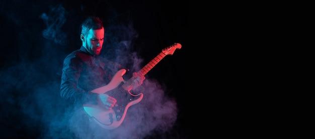 Sylwetka młodego kaukaskiego gitarzysty męskiego odizolowanego na niebiesko-różowym gradientowym tle studio w neonowym kolorze