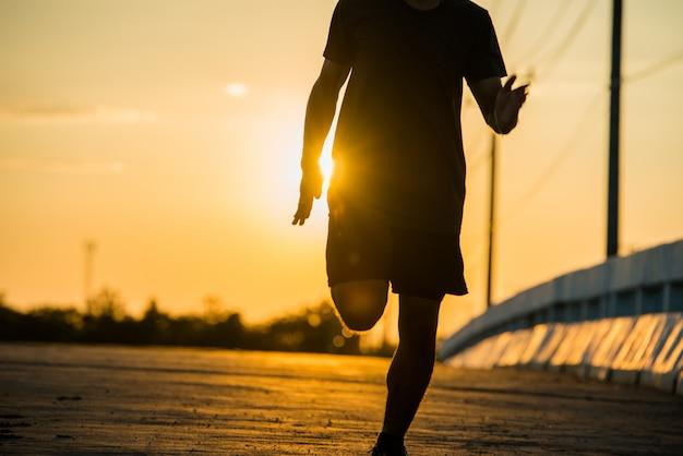 Sylwetka młodego mężczyzny fitness działa na wschód słońca