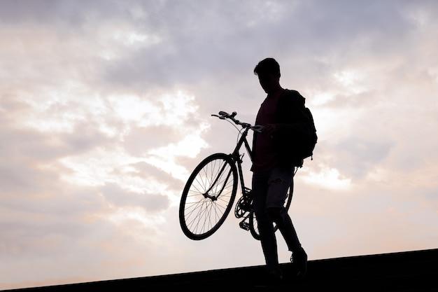 Sylwetka młodego mężczyzny niosącego rower po schodach
