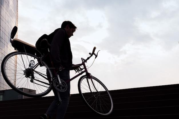 Sylwetka młodego mężczyzny niosącego rower